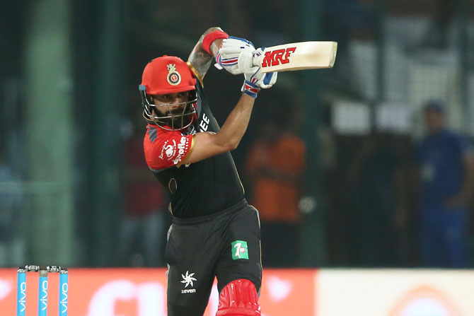 Virat Kohli plays a shot straight down the ground during his innings of 58 against Delhi Daredevils in New Delhi on Sunday