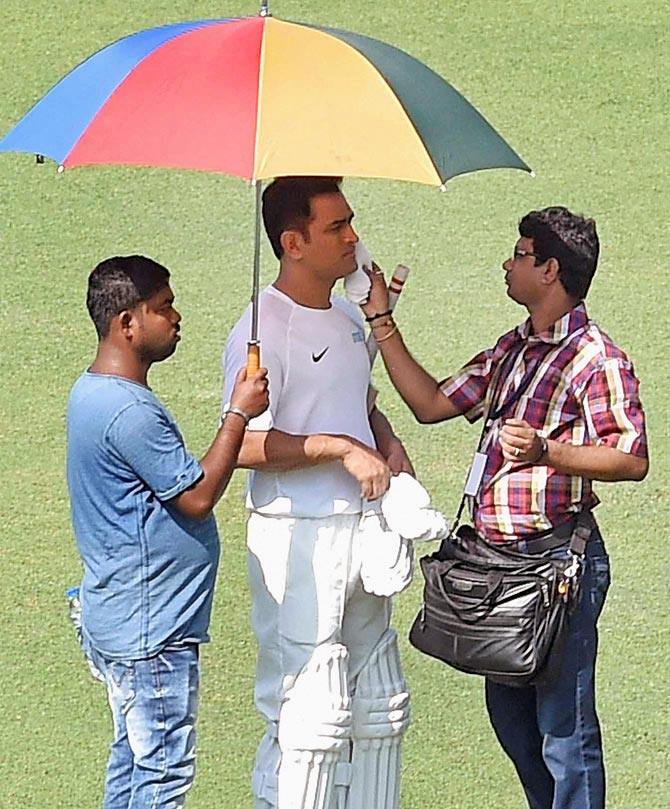 Mahendra Singh Dhoni has make up put on his face in between shots