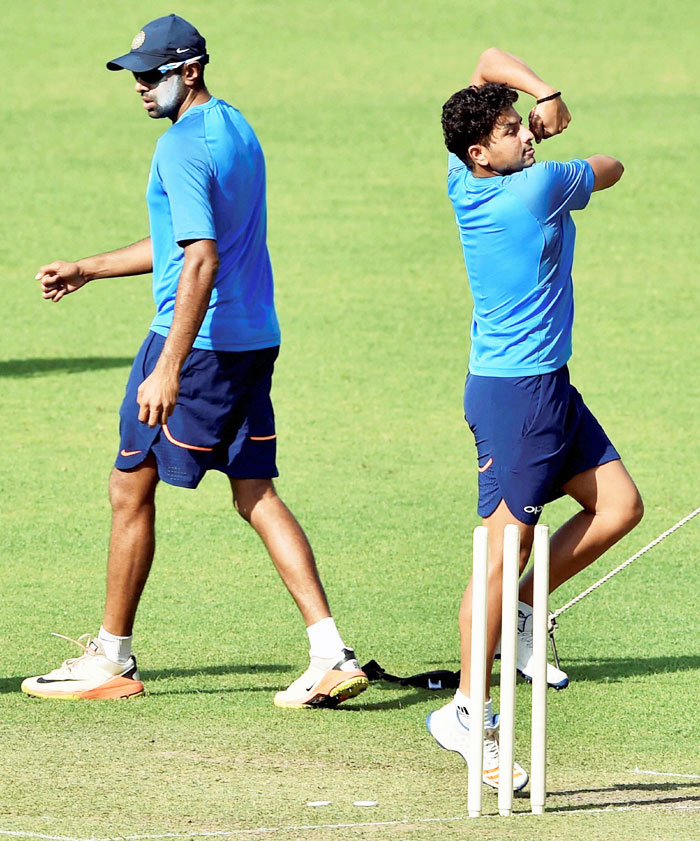 Indian chinaman bowler Kuldeep Yadav rolls his arm over as Ravichandran Ashwin looks on during a training session at Eden Garden in Kolkata on Monday