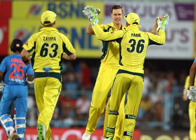 ason Behrendorff, centre, celebrates with team mates after taking the wicket of Rohit Sharma.