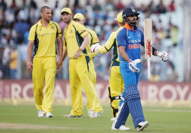 Australia's players celebrate as India captain Virat Kohli walks back after being dismissed