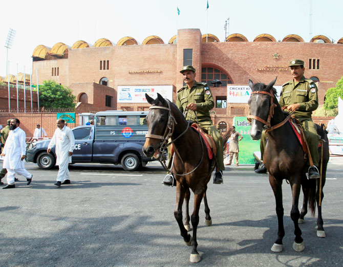 Mounted police officers patrol in front of Gaddafi Cricket Stadium ahead of the World XI cricket series in Lahore