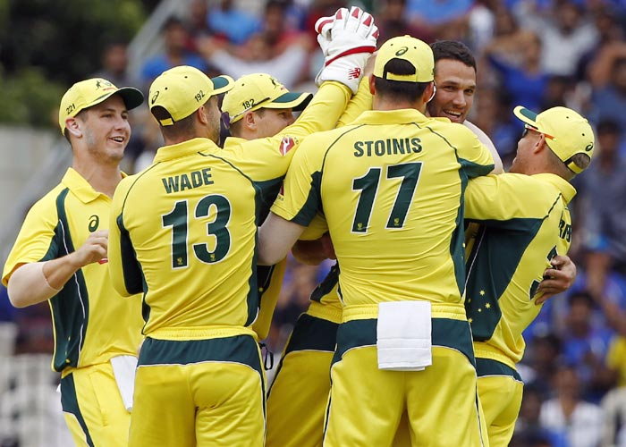 Australia's players celebrate the wicket of Virat Kohli