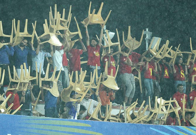 Spectators use plastic chairs in the stands to take shelter from the rain