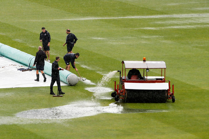 Groundsman work on the pitch during a rain delay