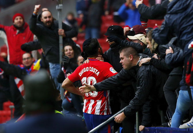 Atletico de Madrid's Diego Costa celebrates with fans after scoring their second goal during the La Liga match against Getafe CF at Estadio Wanda Metropolitano in Madrid on Saturday. His wild celebrations invited a booking