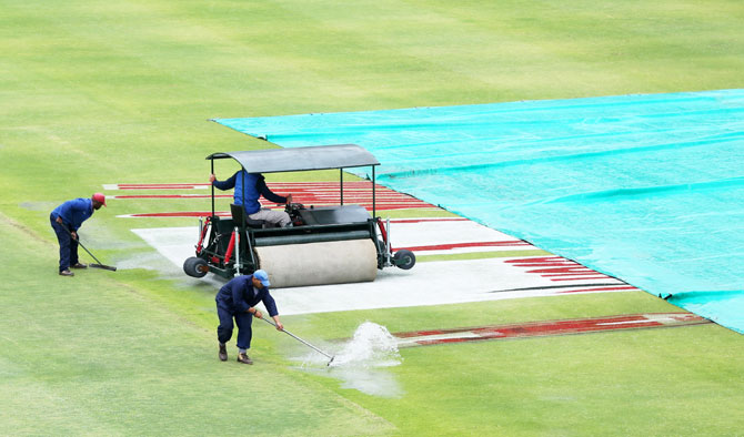 Ground staff workers at Newlands Stadium try to sweep water on the pitch
