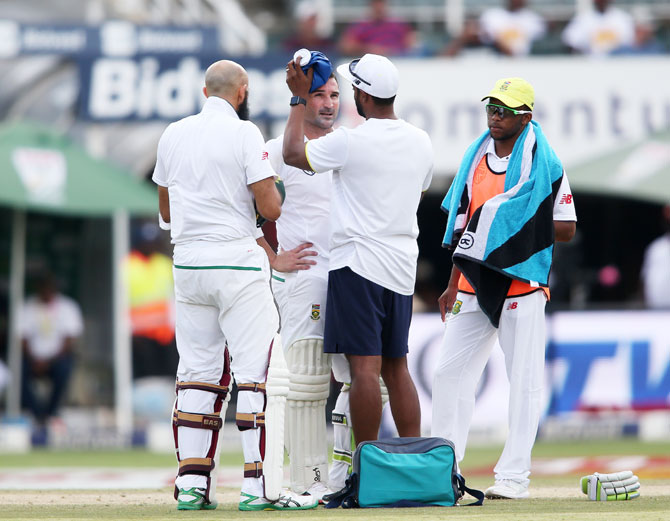 South Africa opener Dean Elgar receives treatment by the team physio after copping one on the helmet off a Bumrah delivery