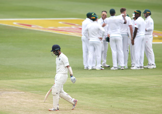 India's Cheteshwar Pujara leaves the field after his dismissal