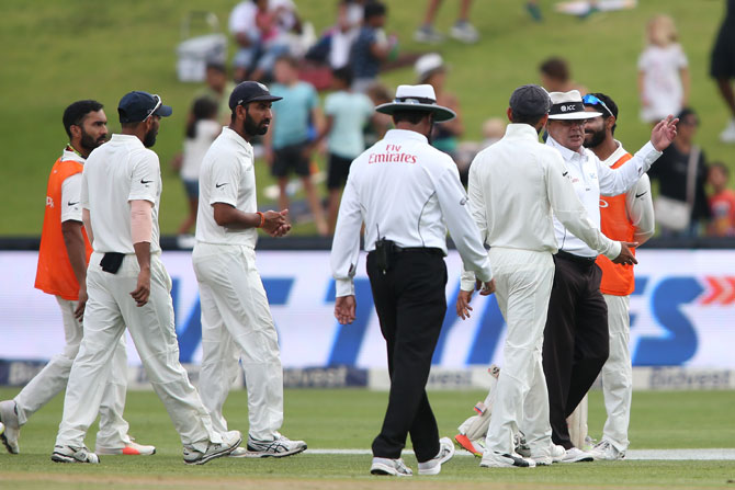Virat Kohli chats with umpires Ian Gould and Aleem Dar as they lead the players off the field