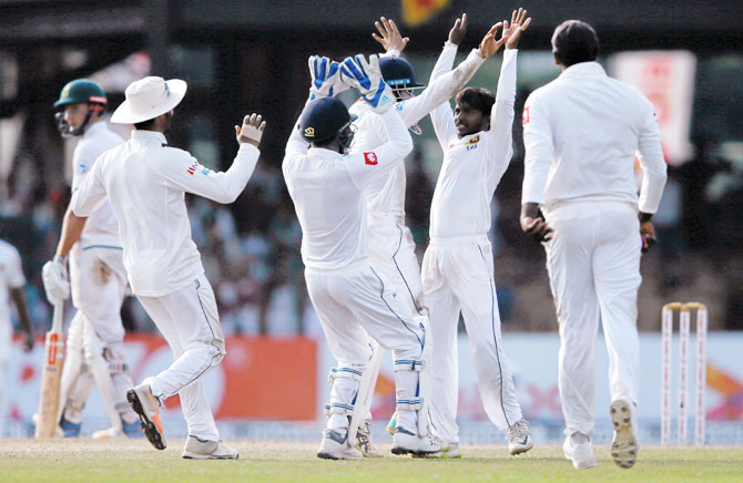 Sri Lanka's Akila Dananjaya (centre) celebrates with his teammates after taking the wicket of South Africa's Keshav Maharaj