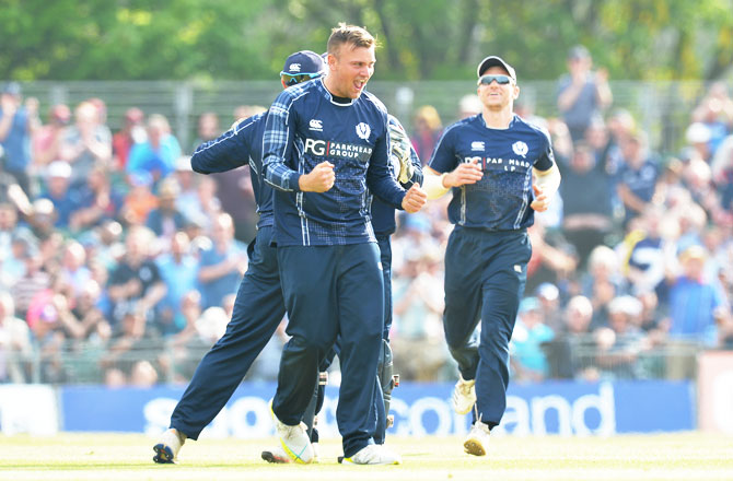 Scotland's Mark Watt celebrates with his teammates after taking the wicket of England's Sam Billings