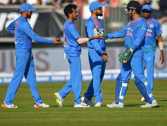 Yuzvendra Chahal celebrates with his team mates after taking the wicket of Andrew Balbirnie