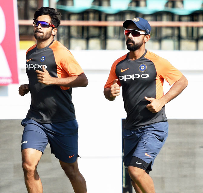 Pacer Shardul Thakur and vice-captain Ajinkya Rahane warm-up at a training session in Rajkot on Wednesday