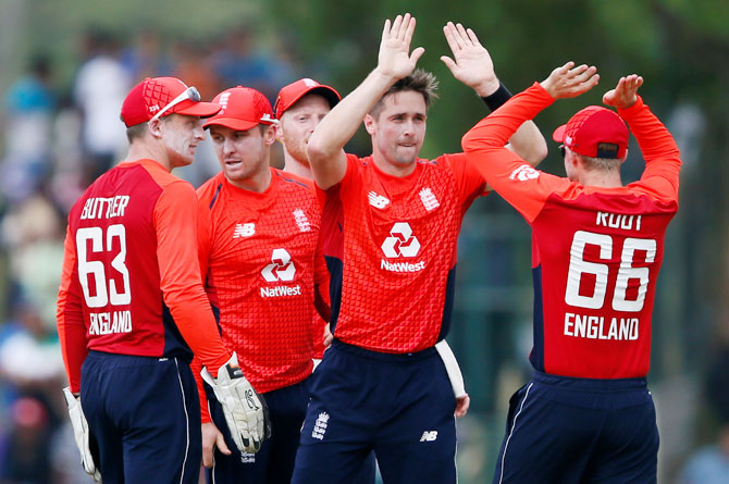England's Chris Woakes celebrates with his teammates after taking the wicket of Sri Lanka's captain Dinesh Chandimal during the 2nd one-day international at Dambulla on Sunday
