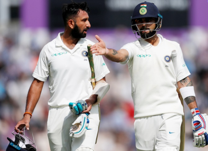 India's Virat Kohli, right, and Cheteshwar Pujara speak as they walk off the field