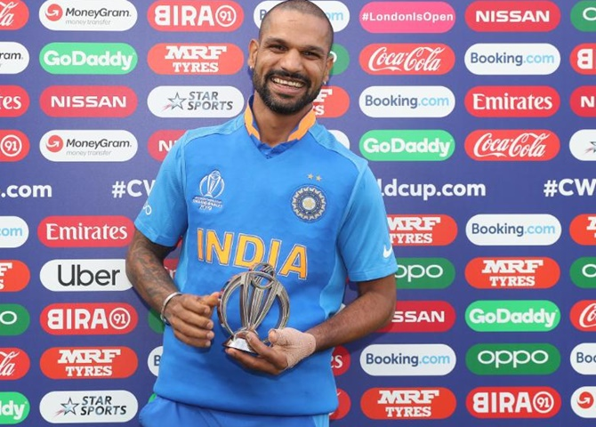 Shikhar Dhawan collecting his  MoM trophy against with a heavily strapped thumb.