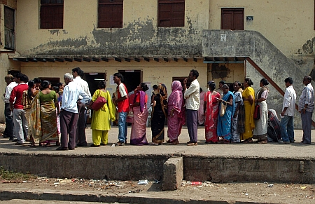People stand in queue to cast their votes at a polling booth in Dharavi