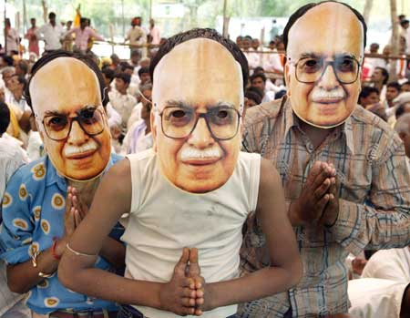 BJP supporters wear masks of party leader Advani in an election campaign rally in Biaora Madhya Pradesh on April 22