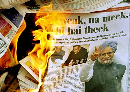 A copy of a newspaper showing photographs of PM Singh burnt by the BJP activists in Mumbai on July 23, 2008