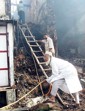 A survivor of the 2002 riots in Gujarat rifles through what is left of his shop in Chota Udaipur, July 7, 2002