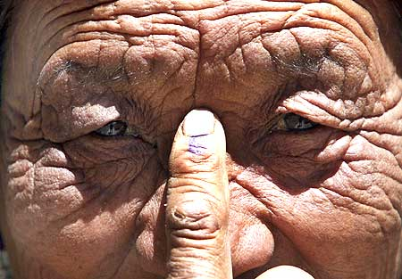 A voter shows her ink-marked finger after she cast her ballot, outside a polling station in  Thiksey, 20 kms east of Leh, on Wednesday