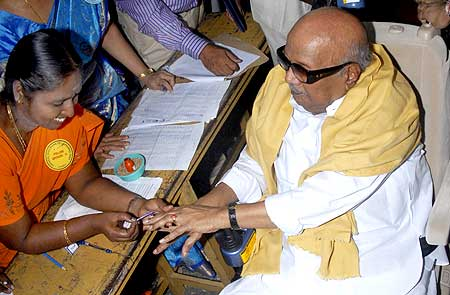 Chief Minister of Tamil Naidu M Karunanidhi gets his finger marked with ink before casting his ballot in Chennai on Wednesday