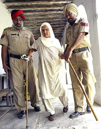 Policemen help a voter to a polling station to cast her ballot in Lopoke village on the outskirts of Amritsar on Wednesday