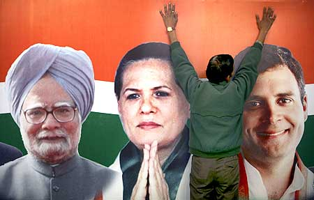 A party worker installs hoarding showing pictures of Dr Manmohan Singh, Congress Chief Sonia Gandhi and her son Rahul Gandhi
