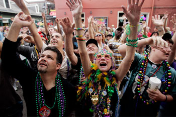 Revelers scream for beads in the French Quarter while celebrating Mardi Gras Day in New Orleans.