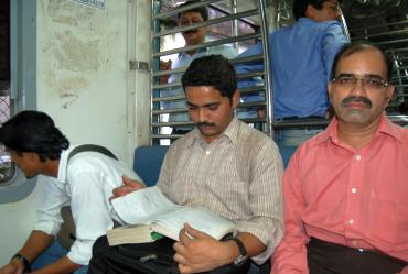 Vaibhav Hatode, centre, studies after boarding a Mumbai suburban train