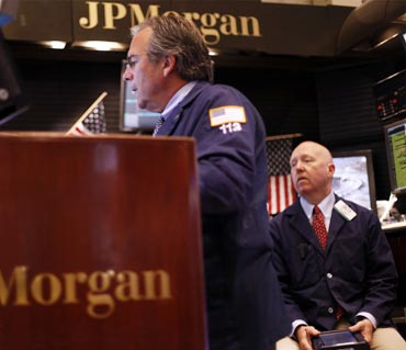 Traders work in the JP Morgan company stall on the floor of the New York Stock Exchange