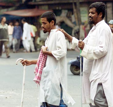 Three blind men help each other cross a busy road in the eastern Indian city of Calcutta