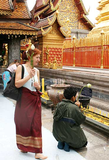 A visitor clasps offerings at the Wat Phrathat Doi Suthep temple.