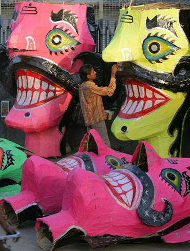 An artist adds the finishing touches to effigies of Ravana in New Delhi.