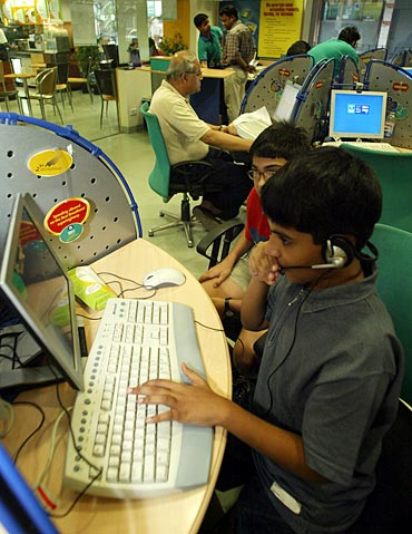 Children play computer games at a high-speed broadband internet cafe in Kolkata.