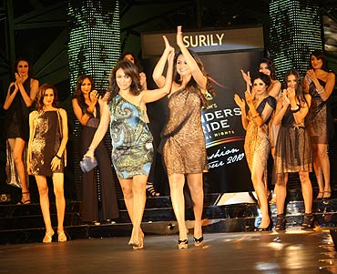 Surily Goel is accompanied down the ramp by Amrita as her models look on
