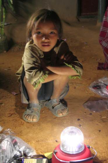 A small tribal child from Manipur stares at the light, a new introduction to her remote village