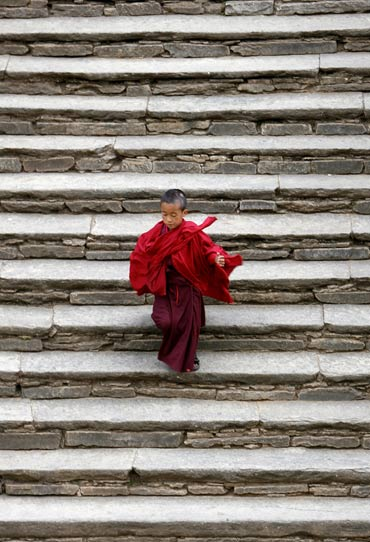 A monk runs down the steps of the Paro Dzong, a fortress.