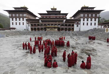 Buddhist monks stand inside the complex of Tashichho Dzong in Thimphu.