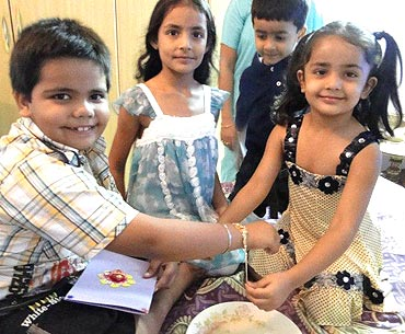 Menka Relhan's son (left) is tied a rakhi by his sister (right)
