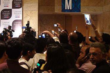 The media and regular attendees scramble to take pictures of the celebrities as they enter the venue