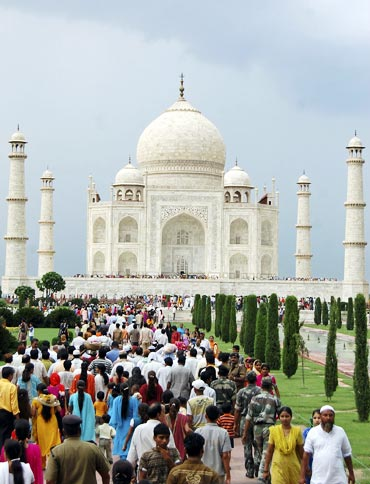 Tourists walk in front of the historic Taj Mahal in the northern Indian city of Agra