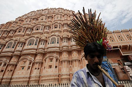 A vendor plays a flute as he tries to attract people to buy flutes in front of Hawa Mahal, also known as Palace of Winds in Jaipur, capital of India's desert state of Rajasthan, August 15, 2010. Hawa Mahal was built in 1799 by Maharaja Sawai Pratap Singh, designed by Lal Chand Usta in the form of the crown of Hindu Lord Krishna and has five stories and is constructed of red and pink sandstone. The side facing the street outside the palace complex has 953 small windows.