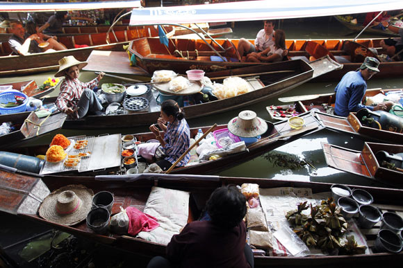 Floating markets in Thailand feature the old style and traditional way of selling goods from small boats on canals between traditional Thai houses and are also popular tourist attractions.