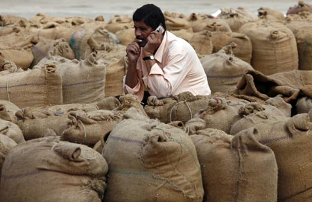 A man speaks on a mobile phone amid sacks filled with wheat and rice inside the market yard of the Agriculture Product Marketing Committee (APMC) on the outskirts of the western Indian city of Ahmedabad November 25, 2010. India's food price index rose 10.15 percent, government data on Thursday showed.