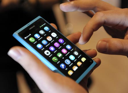 A staff member displays a Nokia N9 smartphone at a news conference in Espoo, June 21, 2011.