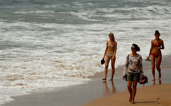 Tourists walk on the Anjuna beach