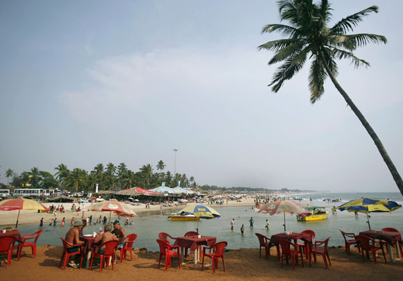 Tourists relax at a cafe on Baga beach in Goa