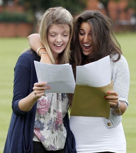 Students Alison Coxon (L, 5 A stars) and Claire Abrahams (3 A stars and one A) react as they open envelopes containing their A level examination results  at Withington Girls School in Manchester, northern England August 18, 2011.